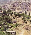 Άποψη του χωριού του Αγίου Αρσενίου στα Φάρασσα. Λαξευτές στο βράχο, οι εκκλησίες της Παναγίας (αριστερά) και του Αγίου Βασιλείου (δεξιά)